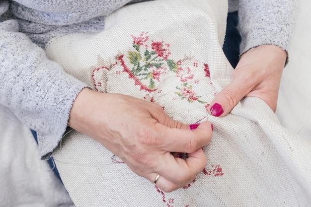 Close-up van de hand die van de vrouw aan een stuk van borduurwerk werkt