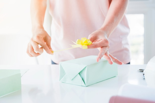 Close-up van de hand die van de vrouw de gele boog op verpakte giftdoos over lijst plakt