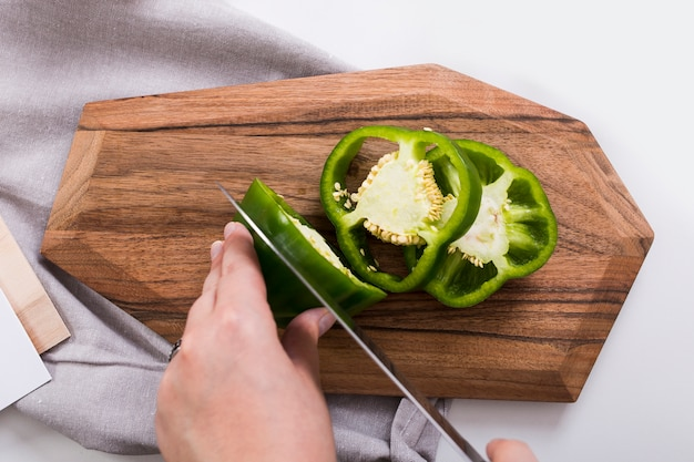 Close-up van de hand die van de vrouw de groene paprika met scherp mes op hakbord snijdt