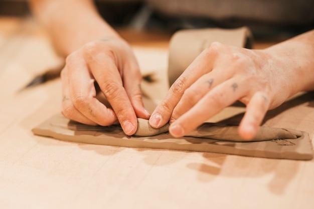 Close-up van de hand die van de vrouw de klei op houten lijst vormt