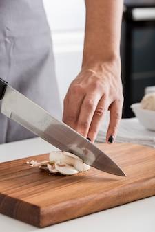Close-up van de hand die van de vrouw de paddestoel met mes op hakbord snijdt