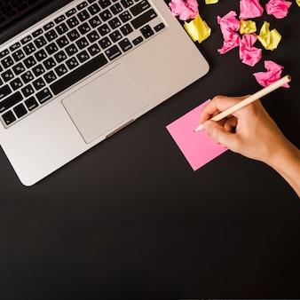 Close-up van de hand die van de vrouw op zelfklevende nota met laptop en verfrommeld document op zwarte achtergrond schrijft