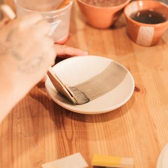Close-up van de hand die van de vrouw schotel in aardewerkworkshop verfraait