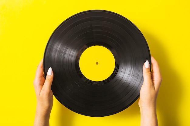 Close-up van de hand die van de vrouw vinylverslag op gele achtergrond houdt