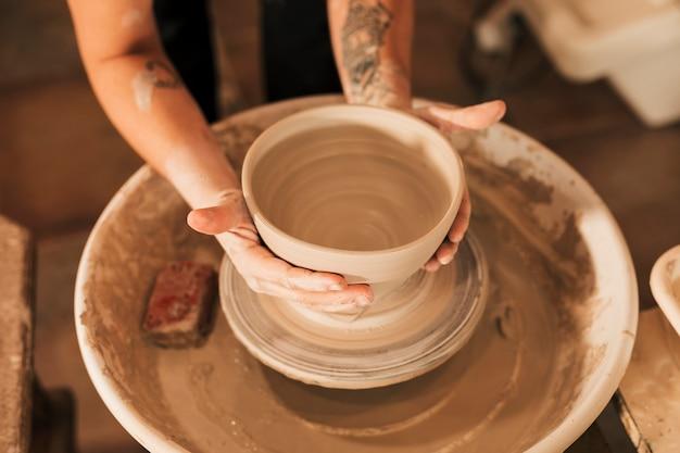 Close-up van de hand die van de vrouwelijke pottenbakker vorm geven aan de kleikom op aardewerkwiel