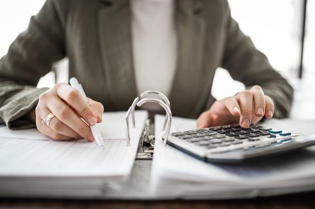 Close-up van de hand die van een accountant op de werkplek berekent