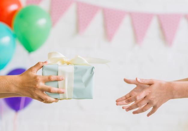 Close-up van de hand die van een jongen verjaardagsgift aan zijn vriend geeft