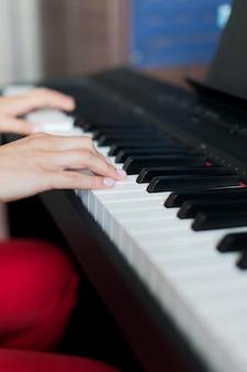 Close-up van de hand die van een klassieke muziekuitvoerder de piano of elektronische synthesizer in muziekschool speelt