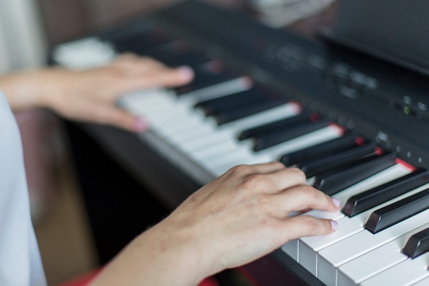 Close-up van de hand die van een klassieke muziekuitvoerder piano of elektronische synthesizer (pianotoetsenbord) ondiepe dof speelt