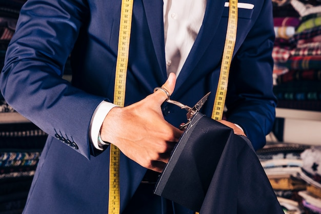 Close-up van de hand die van een mannelijke manierontwerper de stof met schaar snijdt