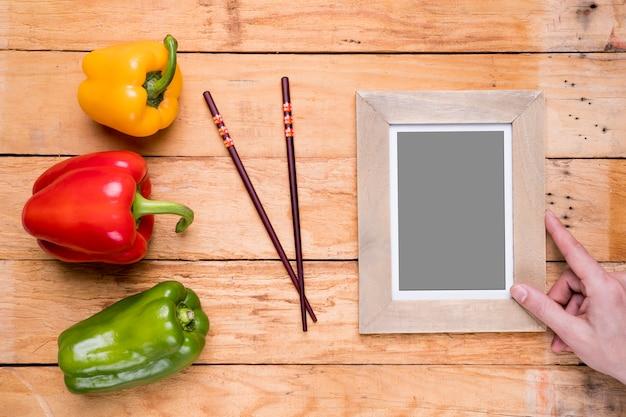 Close-up van de hand die van een persoon de houten omlijsting plaatst dichtbij de groene paprika's en de eetstokjes op lijst