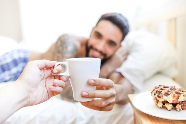 Close-up van de hand die van een persoon kop van koffie geeft aan de jonge mens