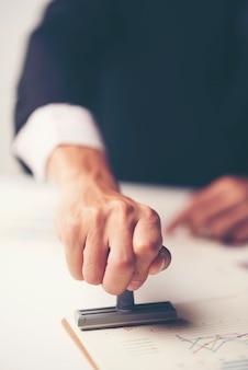 Close-up van de hand die van een persoon met goedgekeurde zegel op document bij bureau stempelen