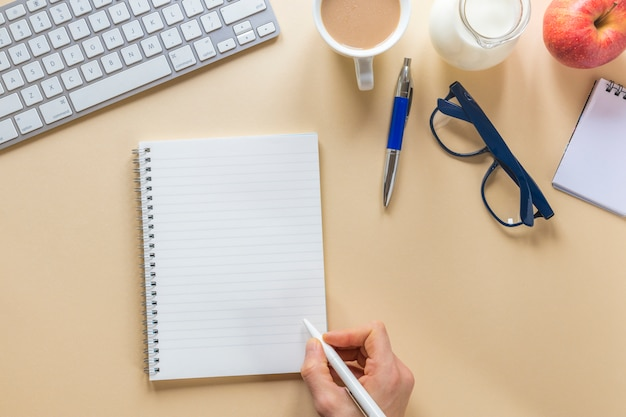 Close-up van de hand die van een persoon op spiraalvormige blocnote met pen op beige bureau schrijft
