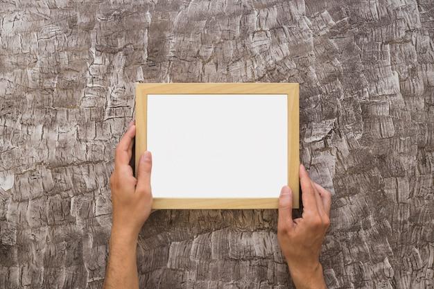 Close-up van de hand die van een persoon witte omlijsting op muur plaatst