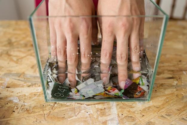 Close-up van de hand die van een vrouw document in water mengt