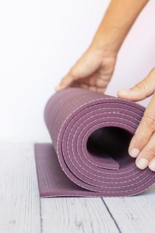 Close-up van de hand die van een vrouw een violette yogamat op wit hout opent