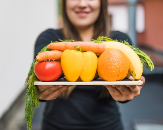 Close-up van de hand die van een vrouw gezond voedsel op lei houdt