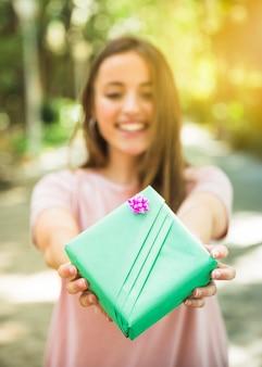 Close-up van de hand die van een vrouw groene giftdoos houdt