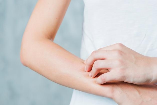 Close-up van de hand die van een vrouw haar hand krast