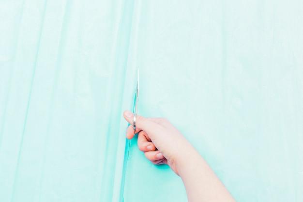 Close-up van de hand die van een vrouw het turkooise gordijn met schaar snijdt