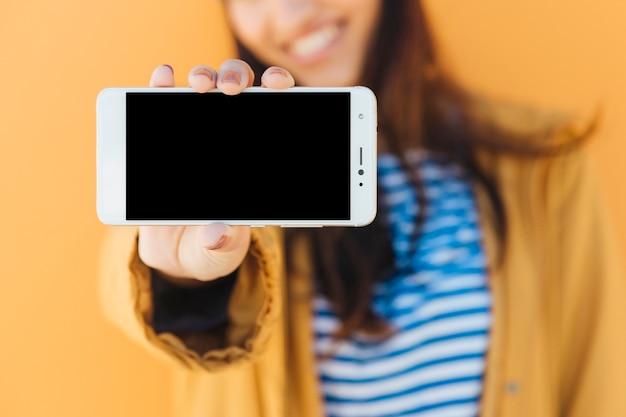 Close-up van de hand die van een vrouw lege het scherm mobiele telefoon toont