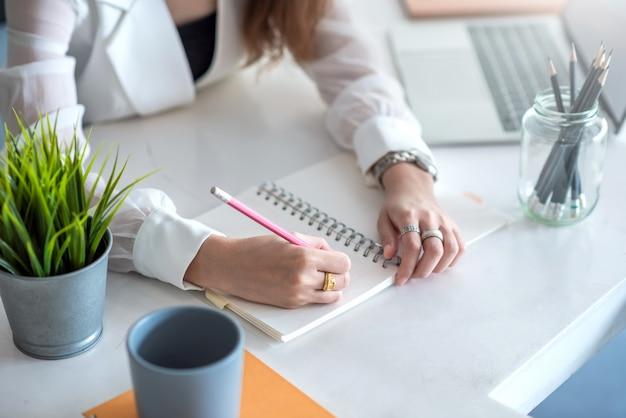 Close-up van de hand die van een vrouw op de agenda op het bureau schrijft