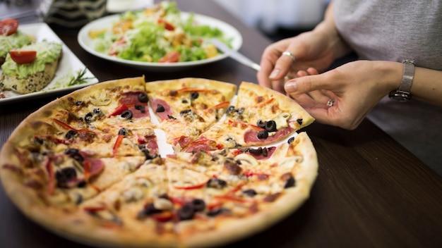 Close-up van de hand die van een vrouw plak van pepperonispizza van plaat neemt