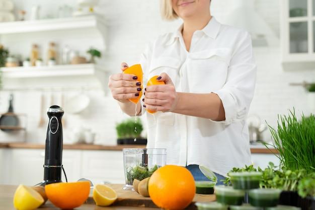 Close-up van de hand die van een vrouw sinaasappelsap knijpt om een smoothie van het tarwesap te maken. whitgrass, gezond eten.