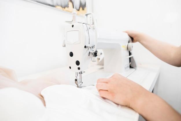 Close-up van de hand die van een vrouwelijke ontwerper aan naaimachine werkt