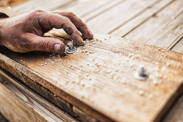 Close-up van de hand een bout in een houten plank schroeven