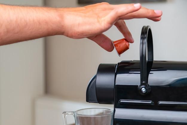 Close-up van de hand een capsule thuis invoegen in een koffiemachine.