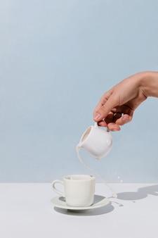 Close-up van de hand gietende amandelmelk van de vrouw in kop van koffie