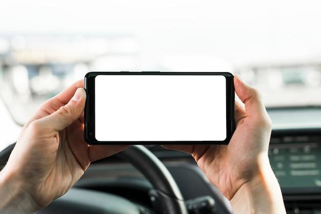 Close-up van de hand houden van mobiele telefoon met lege witte scherm in de auto