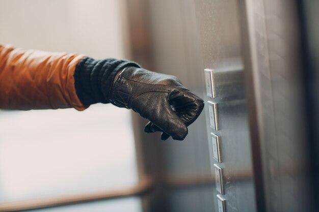 Close-up van de hand in de wijsvinger van de handschoen die op de knoplift drukt tijdens het coronavirus pandemie covid-19 quarantaineconcept
