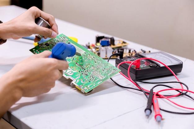 Close-up van de hand mannen houden gereedschap reparaties elektronica fabricage services.