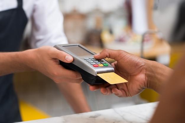 Close-up van de hand met behulp van creditcard veegmachine om te betalen