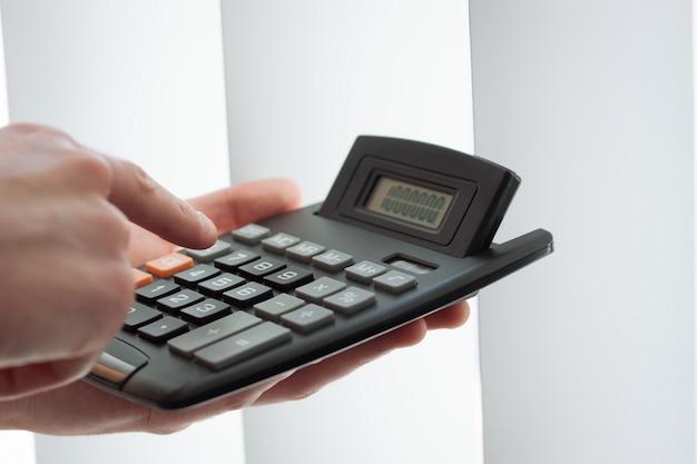 Close-up van de hand met behulp van een rekenmachine