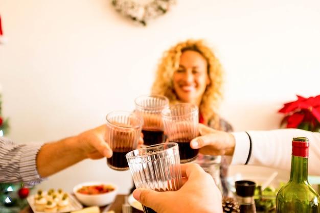 Close-up van de hand met een glas wijn rammelende met andere drie mensen thuis of restaurant samen eten en drinken - krullend en mooie vrouw op de achtergrond