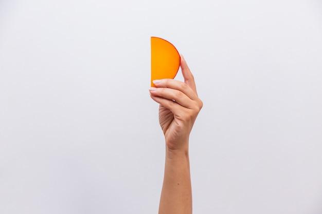 Close-up van de hand met een stuk edammer kaas.