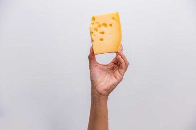 Close-up van de hand met een stuk elementaire kaas.