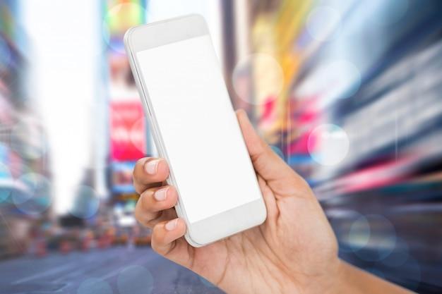 Close-up van de hand met mobiele telefoon over onscherpe stadsgezicht