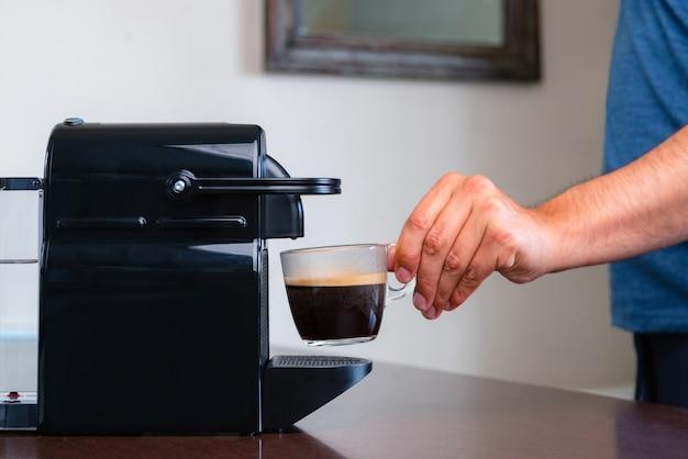 Close-up van de hand oppakken van een kopje espresso capsule koffiemachine thuis.