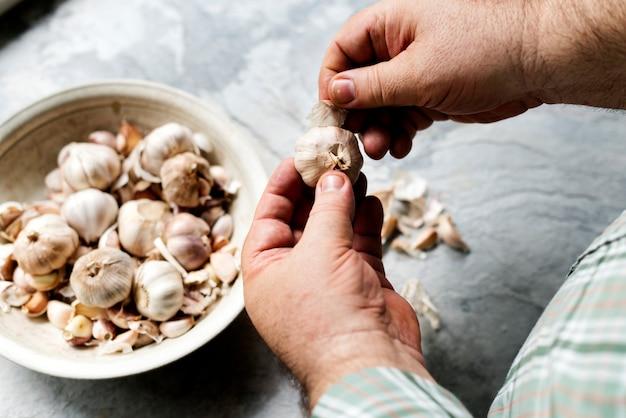 Close-up van de hand peeling knoflook