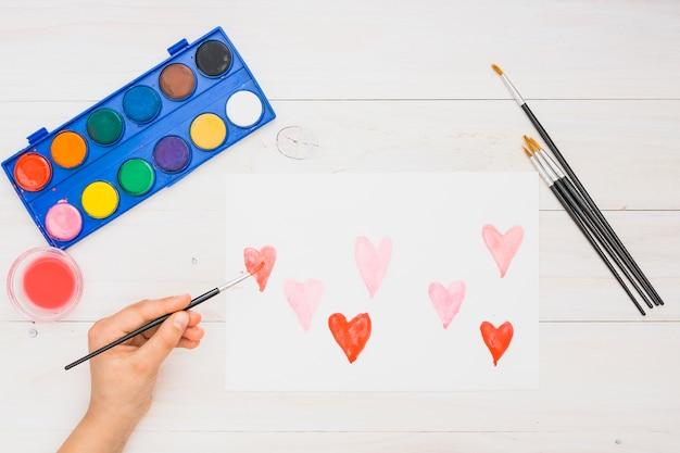 Close-up van de hand schilderij hart vormen met water kleur op wit vel