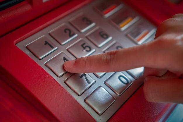 Close-up van de hand te drukken en de verborgen code verborgen bij het opnemen van het geld via atm