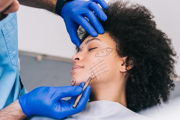Close-up van de hand van de arts die correctielijnen trekt op het gezicht van de jonge vrouw. procedure vóór plastische chirurgie.