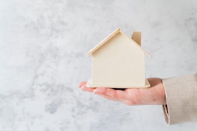 Close-up van de hand van de bedrijfspersoon die houten miniatuurhuismodel houden tegen witte concrete muur