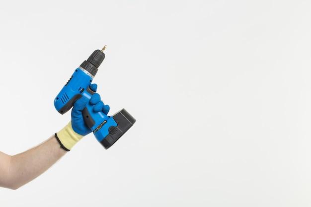 Close-up van de hand van de bouwer met schroevendraaier die handschoenen draagt op een witte achtergrond met kopieerruimte.