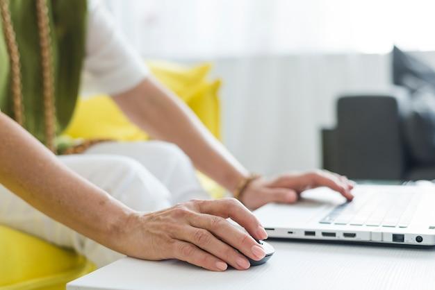Close-up van de hand van de hogere vrouw gebruikend muis en laptop